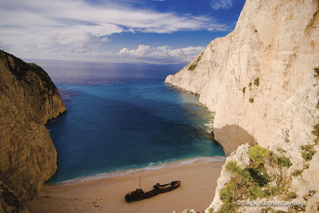 "Shipwreck. It is one of the most famous beaches on the planet and it is the tourist trademark of Zakynthos and Greece. This unique setting was created in 1982, when the ship ""Panagiotis"", carrying illegal cigarettes from Turkey, ran aground due to adverse weather conditions and engine failure. The famous beach is only accessible by boat, although you can admire the view from above on a specially built platform near the village of Maries. (© Nick Kontostavlakis)"